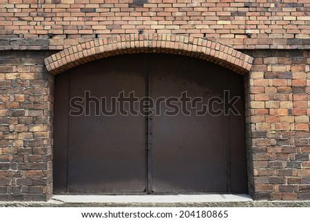 rusted metal door in old brick wall - stock photo