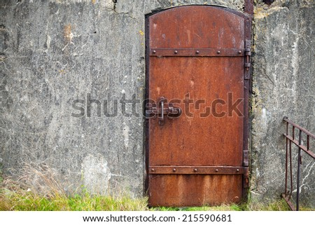 Rusted metal door in old fortification wall, background texture - stock photo