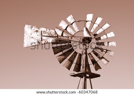 Rusted old Windmill with a sepia tone and copy space - stock photo