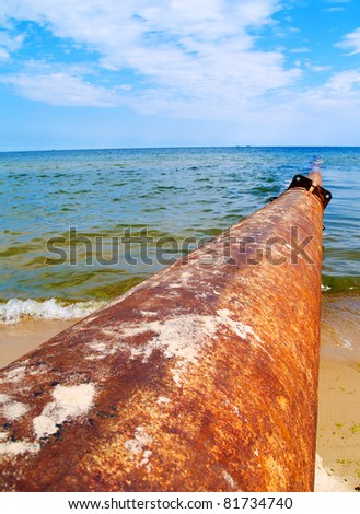 rusted pipe in sea - stock photo