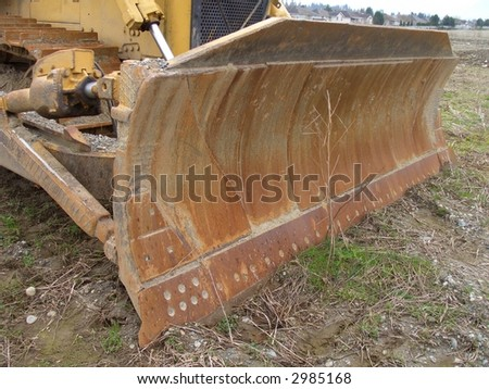 Rusted plow of a track tractor - stock photo