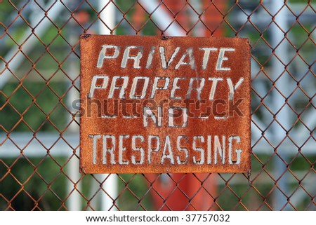 rusted sign on chain link fence - stock photo
