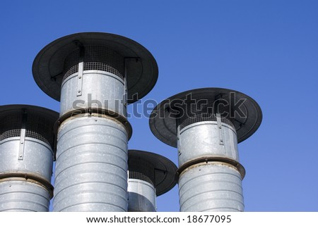 rusted ventilation chimney on a blue sky background - stock photo
