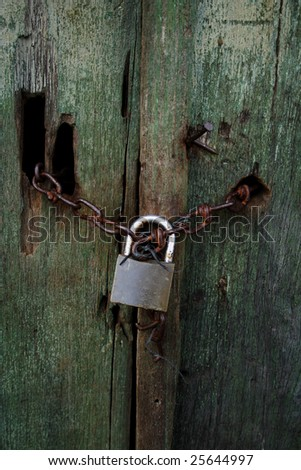 Rusted wood doors of the abandoned house locked with chain and locker.
