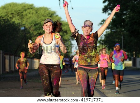 Rustenburg Marathon Club Rainbow Run - NOVEMBER 25: Chearful running young girls covered with powder paint at colour run on November 25, 2015, Rustenburg, South Africa.