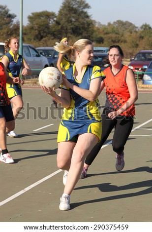 RUSTENBURG, SOUTH AFRICA - June 6:  Korfball League games played at Olympia Park on June 6, 2015 in Rustenburg South Africa.  Ladies team:  Girl trowing ball.