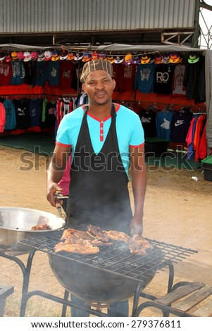 RUSTENBURG, SOUTH AFRICA - MAY 25: African man busy with barbecue  at Rustenburg Fair on May 25, 2014 in Rustenburg South Africa.