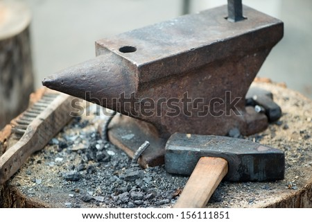 Rustic anvil and hammer on a wooden log, horizontal shot - stock photo