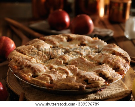 rustic apple pie on wooden table top shot with selective focus
