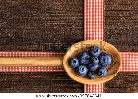 Rustic background with blueberry  on a wooden spoon on a rustic table. - stock photo