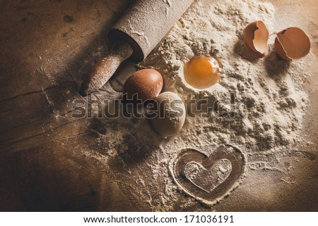 Rustic baking with symbol of heart in flour - stock photo