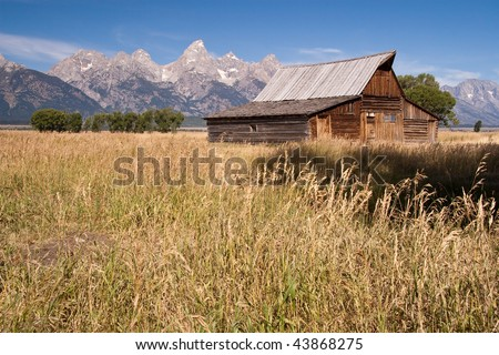 Rustic Barn and Tall Grass in Front of the Grand Teton Mountains - stock photo