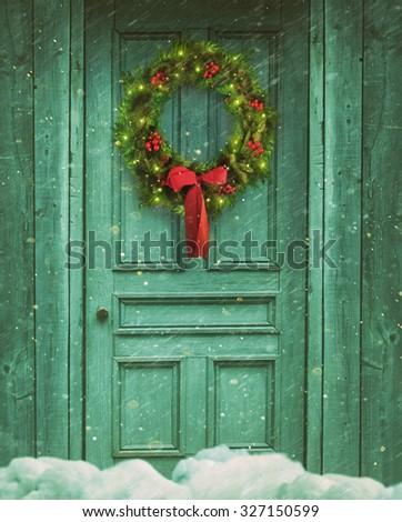 Rustic barn door with Christmas wreath - stock photo