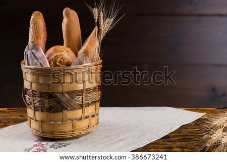 Rustic basket full of assorted fresh crusty bread from the bakery on an old wooden table with copy space behind - stock photo