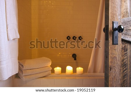 Rustic Bathroom Scene with Towels and Candles - stock photo