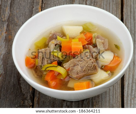 Rustic Beef Soup with Potato, Carrot, Leek and Greens in White Bowl isolated in Wooden background - stock photo