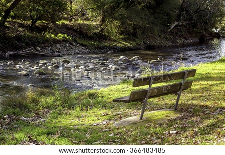 Rustic bench overlooking a tranquil creek. - stock photo