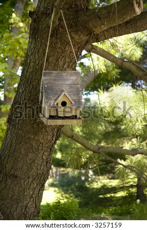 Rustic bird house handing from a tree by a cord or rope. - stock photo