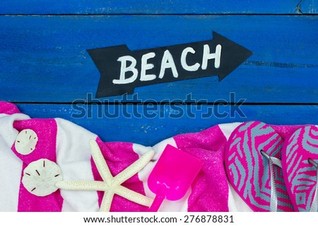 Rustic blue wooden background with arrow BEACH sign by beach towel, sandals, shovel, starfish and sand dollars border - stock photo