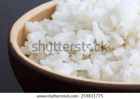 Rustic bowl of cooked white rice on dark surface. Detail. - stock photo