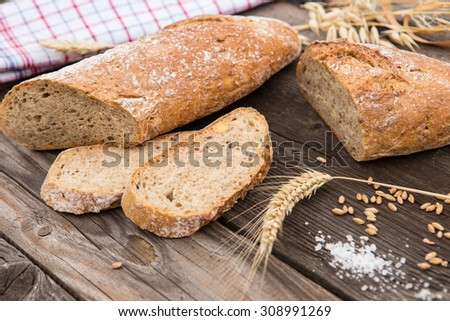 Rustic bread and wheat on an old vintage planked wood table.