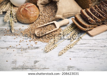 Rustic bread and wheat on an old vintage planked wood table. background with free text space - stock photo