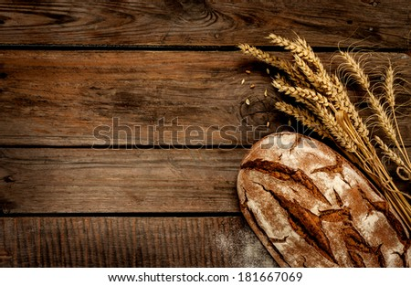 Rustic bread and wheat on an old vintage planked wood table. Dark moody background with free text space. - stock photo