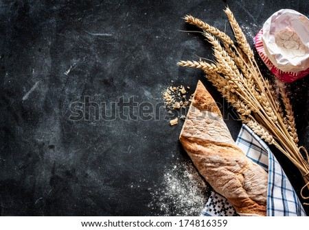 Rustic bread roll or french baguette, wheat and flour on black chalkboard. Rural kitchen or bakery - background with free text space. - stock photo