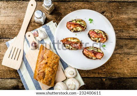 Rustic breakfast - garlic toast, fried mushrooms, scrambled eggs and bacon on top - stock photo