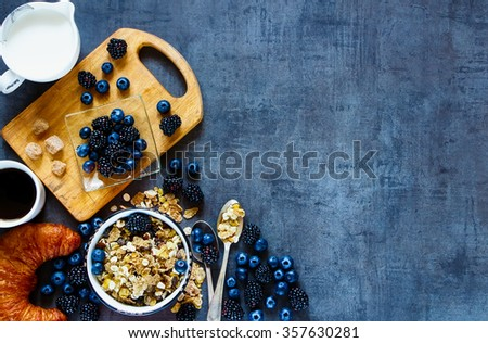 Rustic breakfast table with granola in vintage bowl, dark berries, cup of coffee and croissants on grunge background. Copy space, top view. Organic healthy food and diet concept. - stock photo