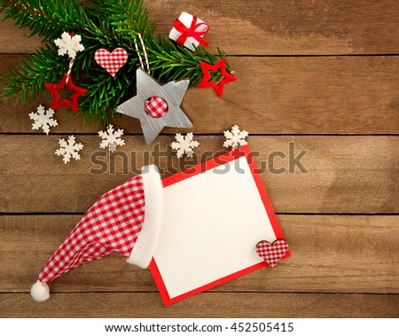 Rustic brown wooden background decorated with green fir branch, red and red and white checkered stars and santa hat with christmas card, gift and snowflakes as christmas decoration in Country Style - stock photo