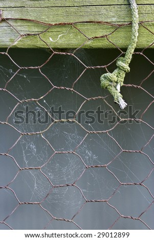 Rustic chicken wire with old rope - stock photo