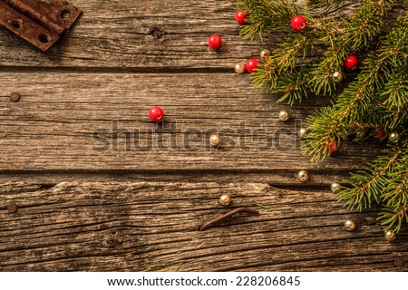 Rustic Christmas Background - Aged Barn Wood with Pine Tree Branch, Red & Gold Beads - stock photo