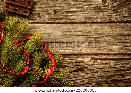 Rustic Christmas Background - Aged Barn Wood with Pine Tree Branch with Red Garland - stock photo