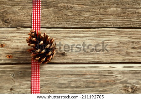 Rustic Christmas background with a decorative white end red checked ribbon and pine cone on wooden boards with copyspace for your seasonal message or greeting - stock photo