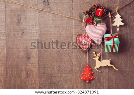 Rustic Christmas decorations hanging over wooden background with copy space - stock photo
