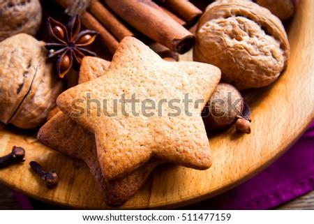 Rustic Christmas gingerbread cookies, nuts and Christmas spices over wooden plate close up