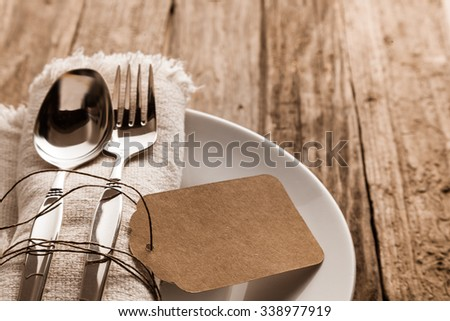 Rustic Christmas place setting with a knife and for on a beige napkin with a blank brown gift tag arranged on a side plate on a wooden table, close up high angle