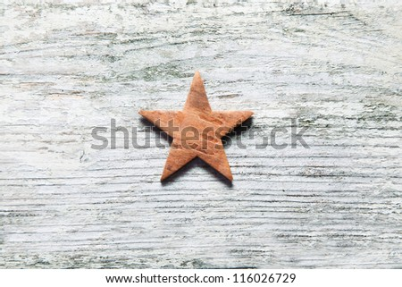 Rustic Christmas star centred on grungy old white weathered wooden boards with grain texture and copyspace - stock photo