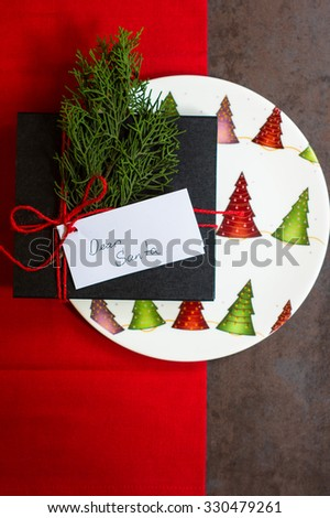 Rustic christmas table setting with bright plates and silverware - stock photo