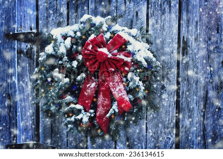 Rustic Christmas wreath on old weathered door with Christmas lights in a snow storm. - stock photo