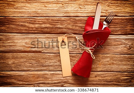 Rustic colorful red Christmas place setting with cutlery wrapped in a red napkin with a gift tag decorated with an Xmas tree on a wooden table with copyspace - stock photo