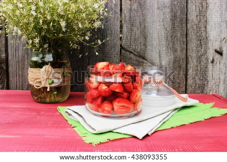 Rustic composition with bowl full of sweet tasty ripe strawberry and bouquet of cute wildflowers in a glass top decorated with jute and wooden ladybirds. Vintage decor for dessert. Romantic style - stock photo