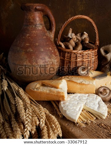 Rustic country still life of bread, cheese and an old wine jar
