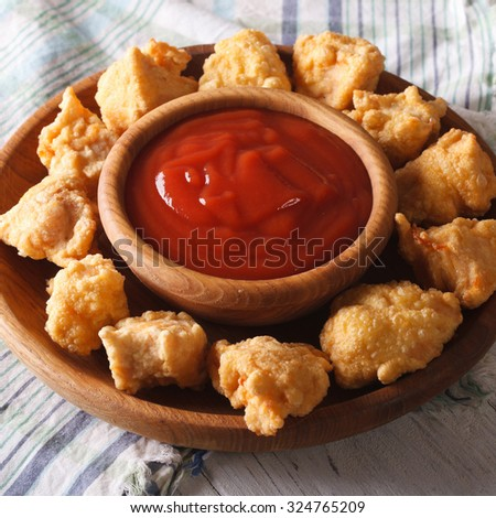 rustic crispy popcorn chicken fillet with sauce close-up on a plate - stock photo