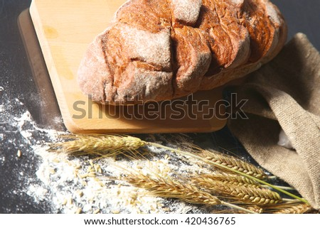 rustic crusty bread and wheat ears on a dark wooden table