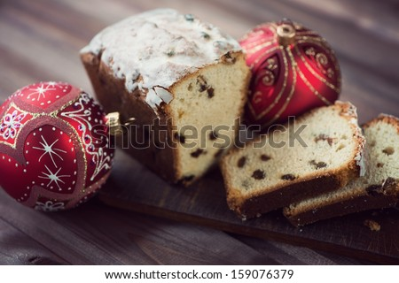 Rustic cutting board with Christmas fruit-cake, studio shot