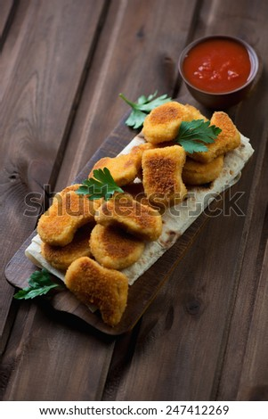 Rustic cutting board with nuggets, parsley and dip sauce - stock photo