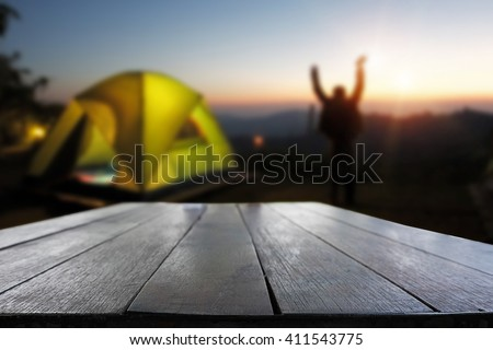 Rustic dark desk space and night camping in forest background. - stock photo