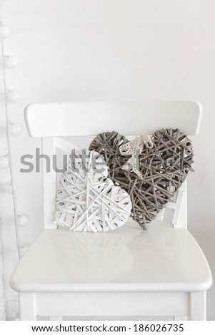 Rustic decor on a white shabby chic chair near the wall - stock photo